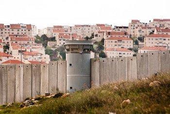 इसराइल द्वारा क़ब्ज़ा किये हुए फ़लस्तीनी क्षेत्र में इसराइल और फ़लस्तीनी इलाक़ों को अलग करने वाली दीवार, जिसके पीछे नज़र आ रही हैं इसराइली बस्तियाँ.