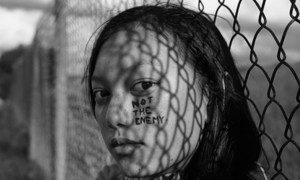 """居住在美国西雅图的索菲亚在社交媒体上分享写有""""不是敌人""""的自拍照。"""