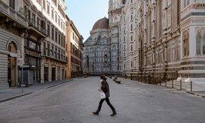 Dans la ville de Florence, en Italie, une personne seule traverse la Piazza Del Duomo désertée pendant le confinement, un espace normalement bondé de milliers de visiteurs.