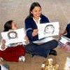 A volunteer helps children draw