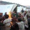 Survivors by a fire in Maidan camp, Pakistan