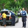 Security forces search vehicles at a check point in Dili