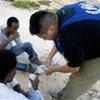 Un employé du HCR discute avec des boat people sur une plage de l'île de Lampedusa. (2007)