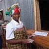 Dans un centre de transit au Burundi, une rapatriée montre l'argent qu'elle a touché pour se réinstaller.