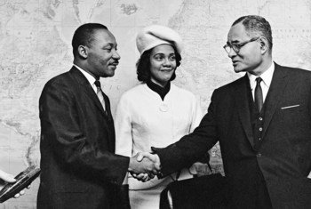 Dr. Martin Luther King and Mrs. King are greeted by Ralph Bunche on a visit to the United Nations in 1964.