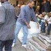 Des étrangers déplacés déchargent des matelas à Germiston (Afrique du Sud).