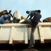 Sudanese refugee clambers onto a repatriation truck to join others returning home from Uganda
