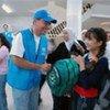 Une fillette iraquienne reçoit du HCR un nouveau sac pour l'école, à Damas (2008).