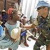 Un casque bleu de la MINUSTAH discute avec une fillette haïtienne.