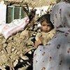Une femme et son enfant devant leur maison détruite par un tremblement de terre au Balouchistan le 29 octobre 2008.