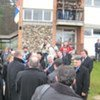 Dignitaries gather in front of the centre as some of the asylum-seekers look on