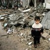 A Palestinian boy amidst the debris of a destroyed house in Gaza City
