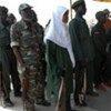 D'ex-combattants du Nord et du Sud Soudan, dont des femmes, remettent symboliquement des armes.