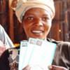 Une femme montre les bons alimentaires qu'elle a reçus du PAM.