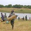 Des civils traversent la rivière Barh Aouk de la République centrafricaine vers le Tchad.