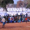 Children and adults queue for safe water near rows of tents provided by UNHCR in the conflict zone in northern Sri Lanka
