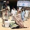 Une famille au Pakistan avec de l'aide fournie par le HCR.
