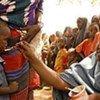 Une femme nourrit un enfant avec de la nourriture thérapeutique en Somalie.