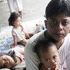 Ryan Leyva, 25, ponders the future with his children at an evacuation centre in the Philippines