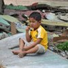 A child sits alone amid the ruins of a collapsed building in Padang, West Sumatra, Indonesia