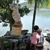 An earthquake survivor washes dishes by the river at Muaro Village in West Sumatra, Indonesia