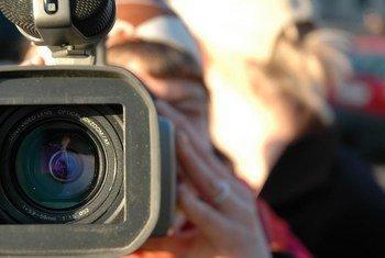 Une journaliste reporter d'images couvrant un évènement pour sa chaine de télévision