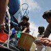 Quake survivors get fresh water from water tank at Muaro Village, West Sumatra