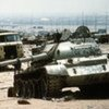 A destroyed Iraqi battle tank amidst other vehicles on the highway between Kuwait City and Basra, Iraq in April 1991