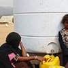 Children getting safe water from a UNICEF-supplied tank at the Mazraq camp in northern Yemen