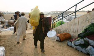 A displaced man from South Waziristan collects a package of aid from UNHCR