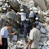 Secretary-General Ban Ki-moon (left) stands beside the remains of UN Headquarters in Port-au-Prince, Haiti.