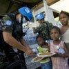 Des casques bleus distribuent de l'eau et des repas à des enfants de Cité Soleil, un quartier de Port-au-Prince.