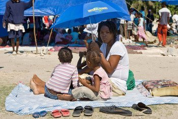A mother shelters her children from the sun in Cité Soleil, Haiti.
