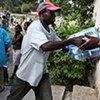 Des travailleurs humanitaires distribuent de l'eau fournie par l'UNICEF à un orphelinat à Port-au-Prince.