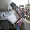Haitians displaced by the powerful earthquake receive water out of a truck in the Canapé-Vert, Port-au-Prince