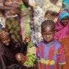 Un enfant au Niger attendant la nourriture qui l'empêchera d'être victime de malnutrition.