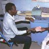 A health worker in Sudan dispenses multidrug therapy to an elderly leprosy patient