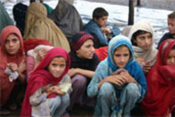 Crianças deslocadas aguardam pacotes de comida do Ramadã no acampamento Jalozai, no Paquistão