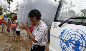 UN aid worker distributes blankets to survivors displaced by cyclone Nargis, Myanmar