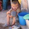 A boy drinks water in the resettlement camp in Khuroson District, Tajikistan