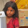 A young Pakistan girl gets foods and water from WFP