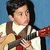 Un enfant rom jouant de la guitare. Photo UNESCO/Michel Ravassard