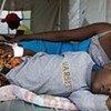 Une femme est allongée à côté de son fils qui reçoit un traitement contre le choléra en Haïti.