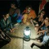 Children sit around the 2009 SEED Gold Award project, solar-powered lights made from recycled kerosene lanterns