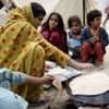Flood victims gather around their meal at a tent camp in Quetta, Balochistan Province, Pakistan