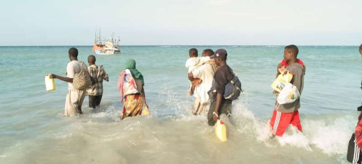 People waiting to board a boat to take them across the Gulf of Aden.