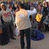 Un employé de l'ONU parle avec un groupe de travailleurs migrants qui viennent de franchir la frontière entre la Libye et la Tunisie, à Ras Adjir.