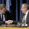 Alain Le Roy (left) and Yury Fedotov shake hands after signing pact to fight organized crime in conflict areas