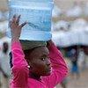 Une jeune fille haïtienne transporte de l'eau à Port-au-Prince.