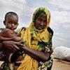 Une femme somalienne avec un enfant attend de pouvoir s'enregistrer pour obtenir de la nourriture dans un camp près de la frontière entre le Kenya et la Somalie.